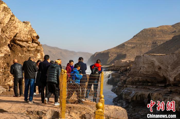 图为游客在岸边观赏瀑布拍照留念。 兰华 摄