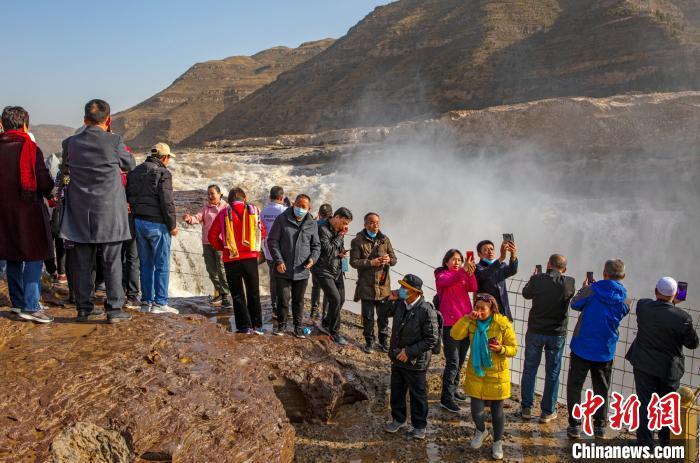 图为游客在陕西黄河壶口岸边近距离观赏瀑布。 兰华 摄